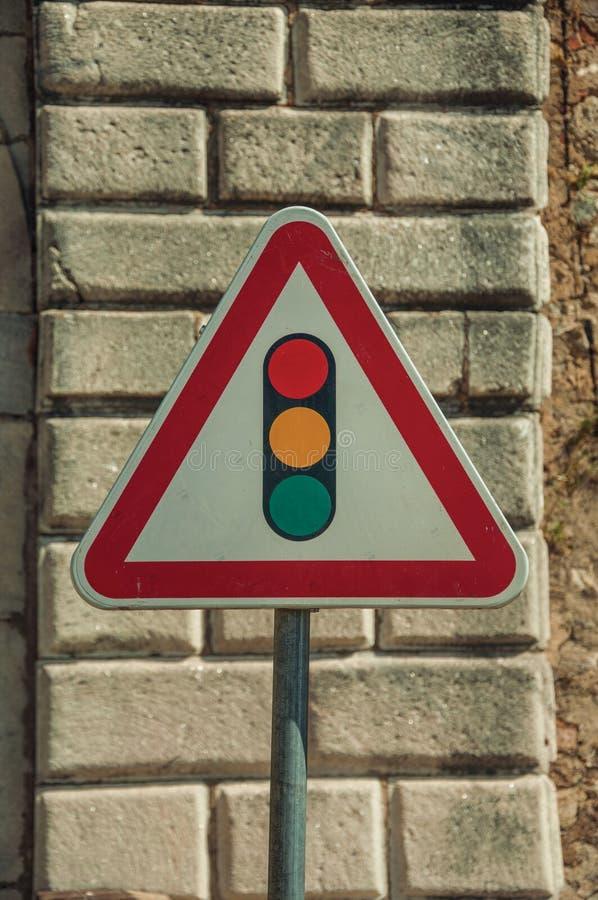 交通信号在石砖墙前面的前面路标 免版税库存照片