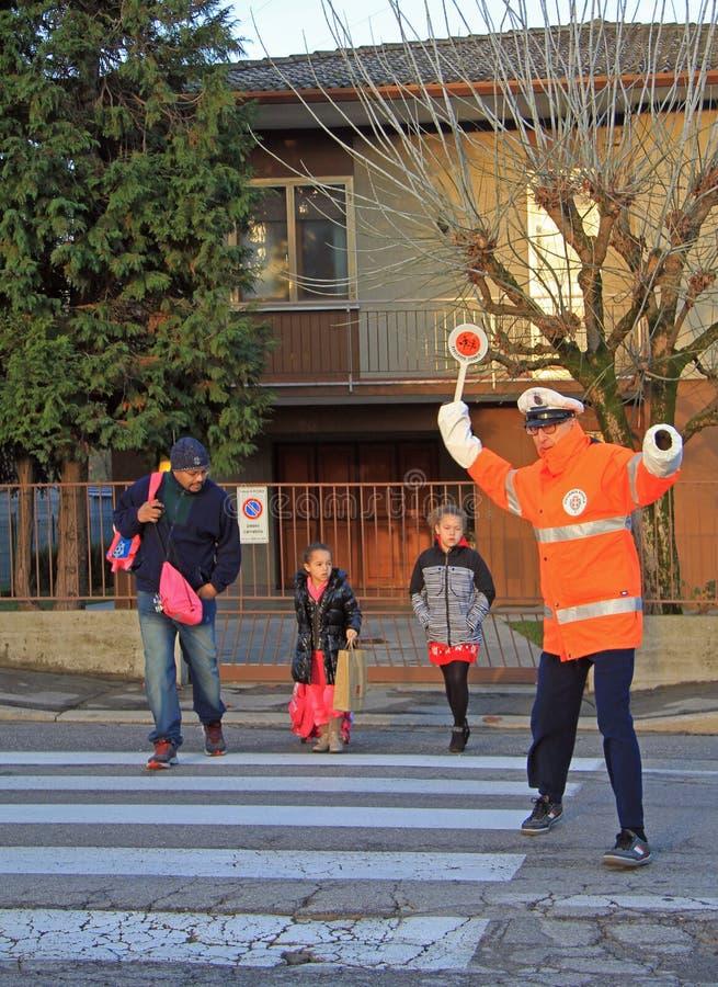交通控制器帮助横渡一条行人交叉路 库存照片