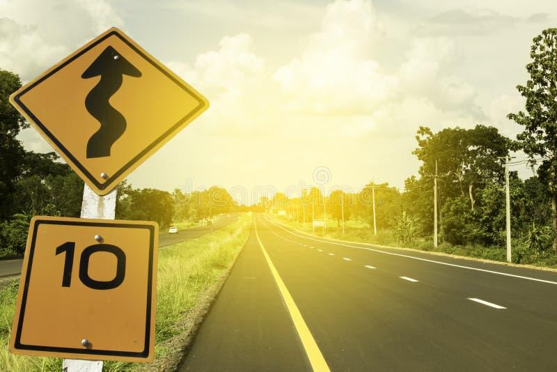 交通标志、10英里/小时和弯曲道路小心标志安全驱动的在国家黑色路,天空与音色 免版税库存照片