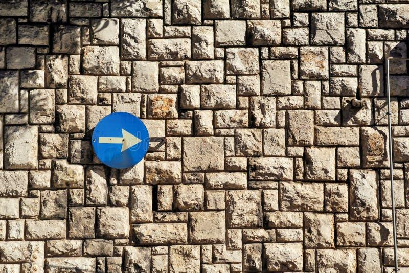 交通标志一方式与一个箭头的路牌在一个石墙上是纹理和材料的样式与色的石头 免版税库存图片