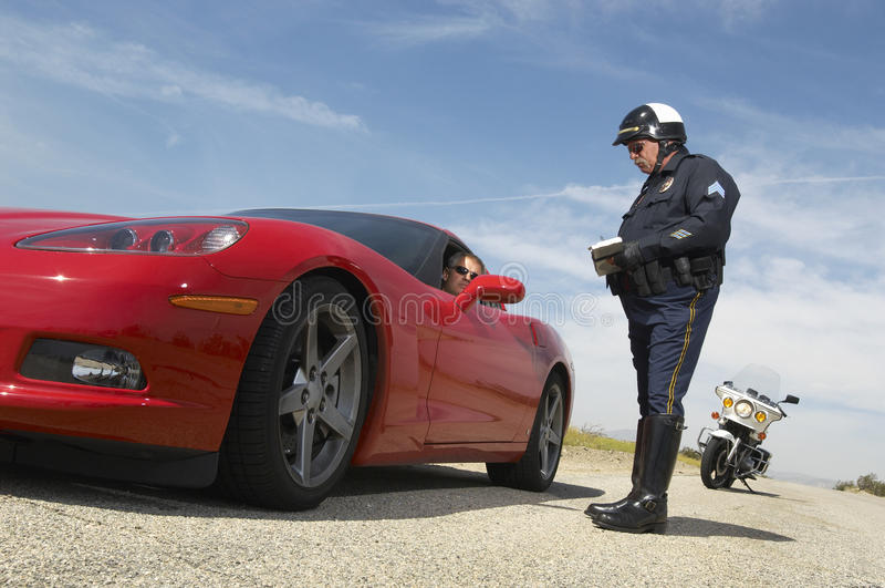 交通警谈话与跑车司机  免版税库存图片
