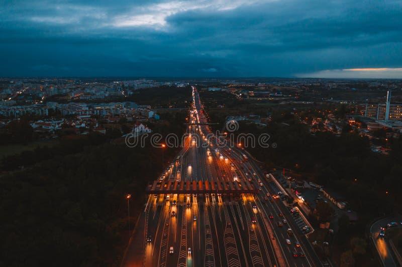 交通路的空中夜视图有穿过问题的汽车的通行费高速公路,通行费驻地 免版税库存图片
