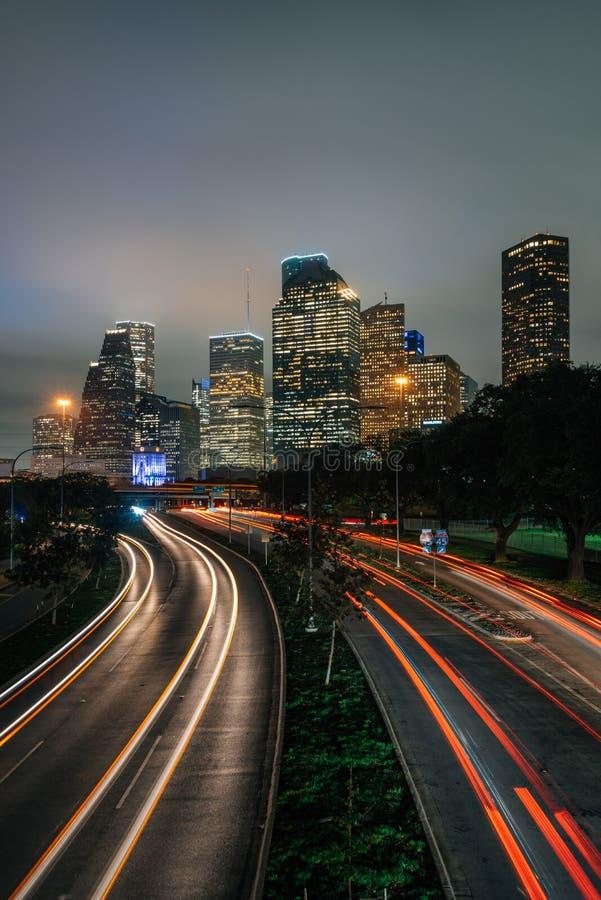 交通长的曝光在亚伦大路的和休斯敦地平线在晚上,在休斯敦,得克萨斯 免版税库存照片