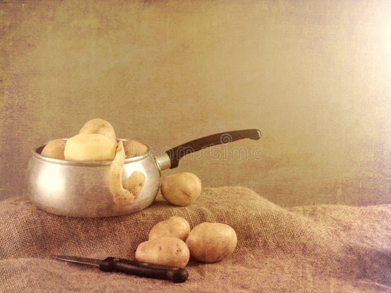 亦称食物配制,在农舍土气设置静物画的被剥皮的土豆与平底深锅,刀子,粗麻布黄麻 免版税库存照片