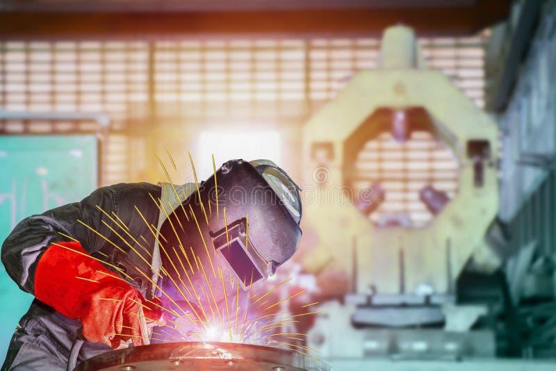 产业工人在焊接的MIG焊接工厂与火花光 免版税库存照片