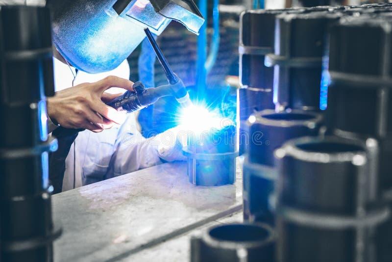 产业工人在研的制造工厂完成金属管子 免版税库存照片