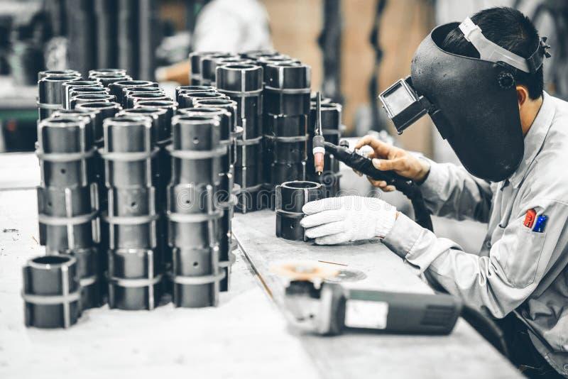 产业工人在研的制造工厂完成金属管子 图库摄影