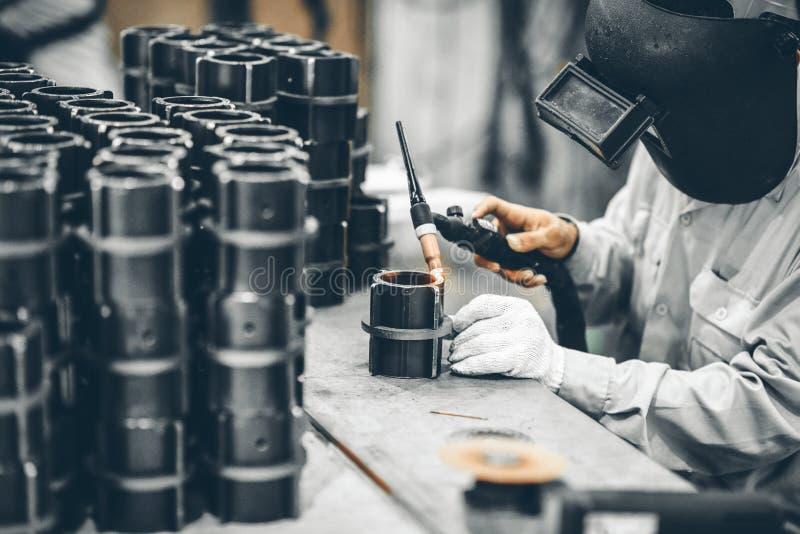 产业工人在研的制造工厂完成金属管子 免版税库存图片