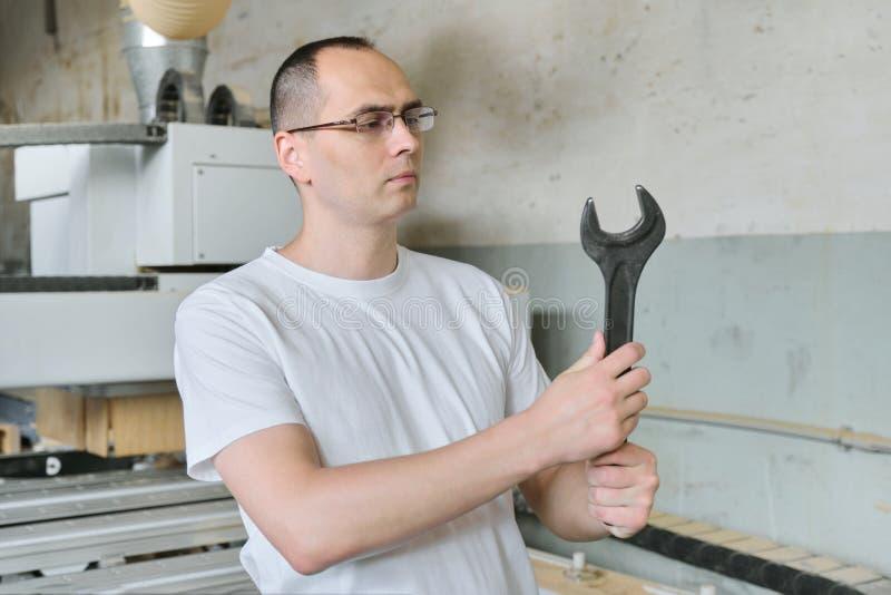 产业工人画象有工具、工作员藏品板钳或者扳手的 免版税库存照片