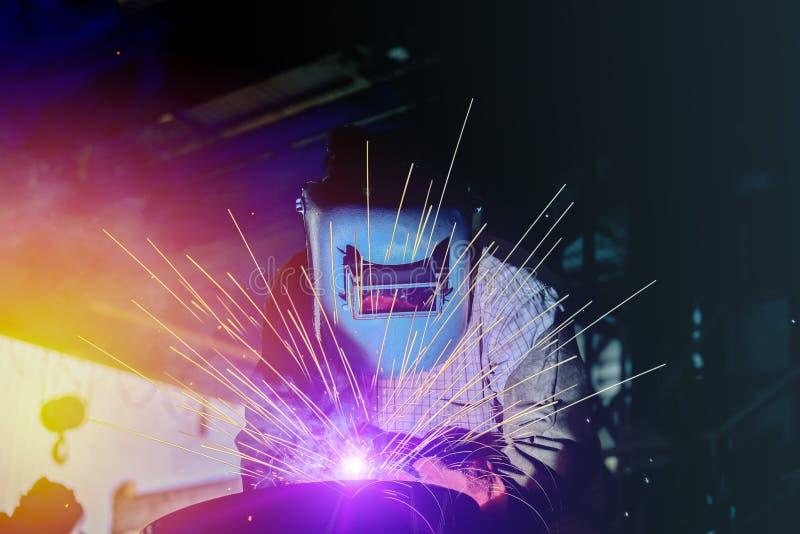 产业工作者焊接的钢管在有sparkslight的工厂 图库摄影