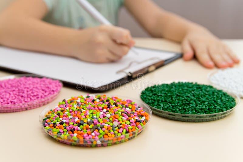 产业的实验员检查塑料药丸 在粒子的塑料原材料 聚合物,塑料树脂 免版税库存照片