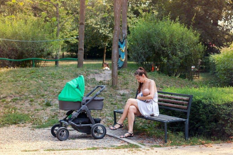 产假的新的妈妈与外面她的婴孩为走的婴儿推车,她坐新出生的公园长椅和哺乳 免版税库存图片