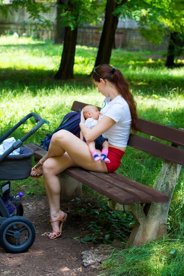 产后的新的母亲第一次是外面与她新出生的婴孩,哺乳婴儿和坐公园长椅 库存图片