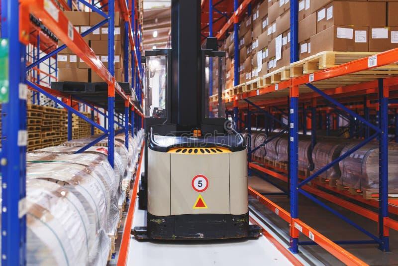 产品、材料和物品地址存贮系统在仓库里 在行之间的被处理的电铲车 免版税库存图片