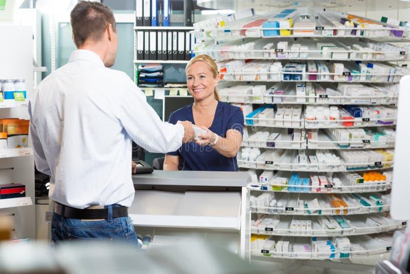 给产品的成熟化学家药房的顾客 免版税库存照片