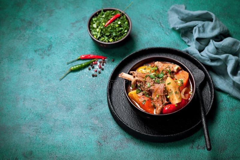 产小羊肉被炖的Khashlama用土豆、红萝卜、胡椒和香料 库存照片
