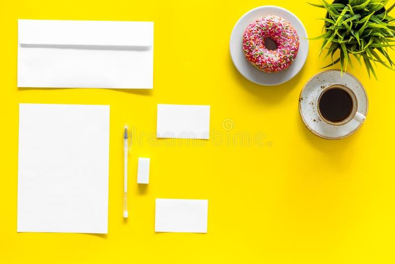 产生品牌身份 烙记的空白的文具在咖啡和多福饼附近在黄色背景顶视图大模型 库存图片