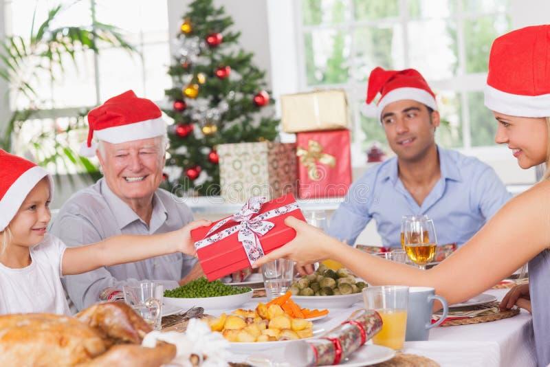 产生女儿圣诞节礼物的母亲 免版税库存图片