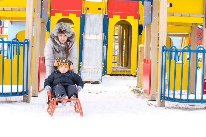 产生她的新儿子雪橇乘驾的妈咪 库存照片
