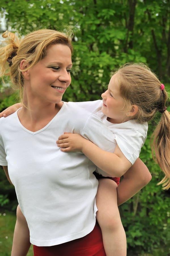 产生她的母亲肩扛乘驾年轻人的子项 库存照片