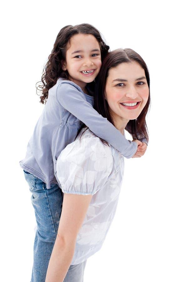 产生她的母亲肩扛乘驾的快乐的女儿 库存图片