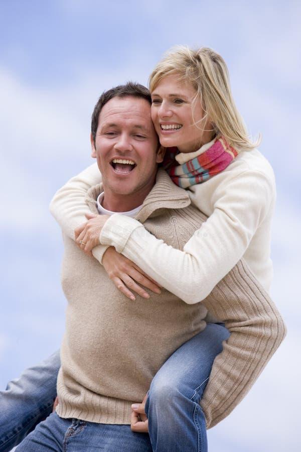产生户外人扛在肩上乘驾微笑的妇女 免版税库存照片
