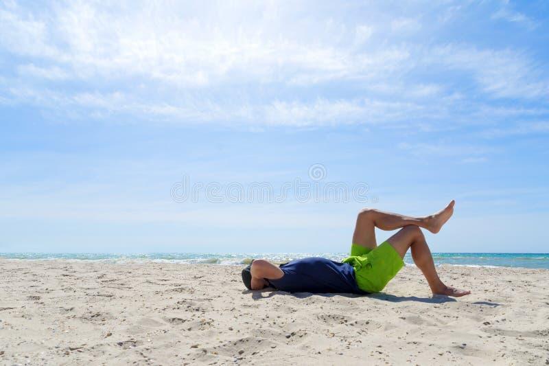 享受一个假期,与他的腿的暂停使用的年轻人在海岸, 免版税库存照片