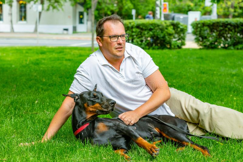 享受一个晴天的年轻人在有他的狗的公园 Dobermann 他们演奏一起说谎在绿草 免版税库存图片
