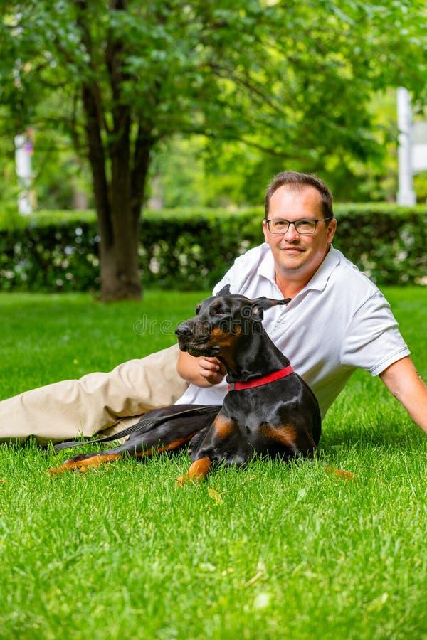 享受一个晴天的年轻人在有他的狗的公园 Dobermann 他们演奏一起说谎在绿草 库存图片