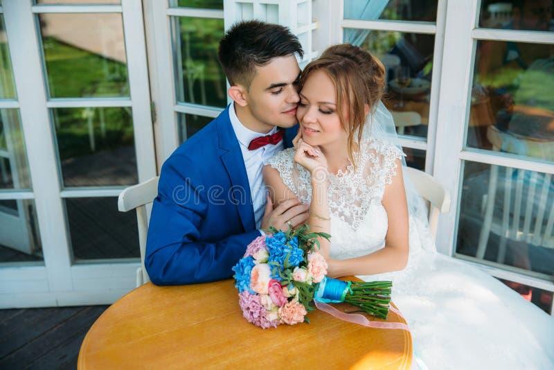享受一个温暖的夏日的新婚佳偶一对美好的夫妇  一个人轻轻地拥抱他心爱,在桌谎言花束 库存图片