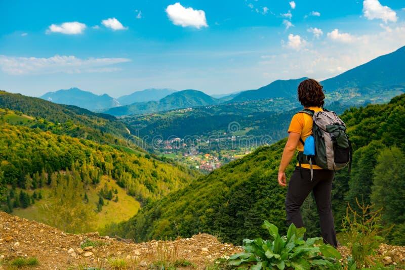 享受一个美好的山风景的年轻山徒步旅行者报道用豪华的森林 远足在一个晴朗的夏日 免版税库存图片