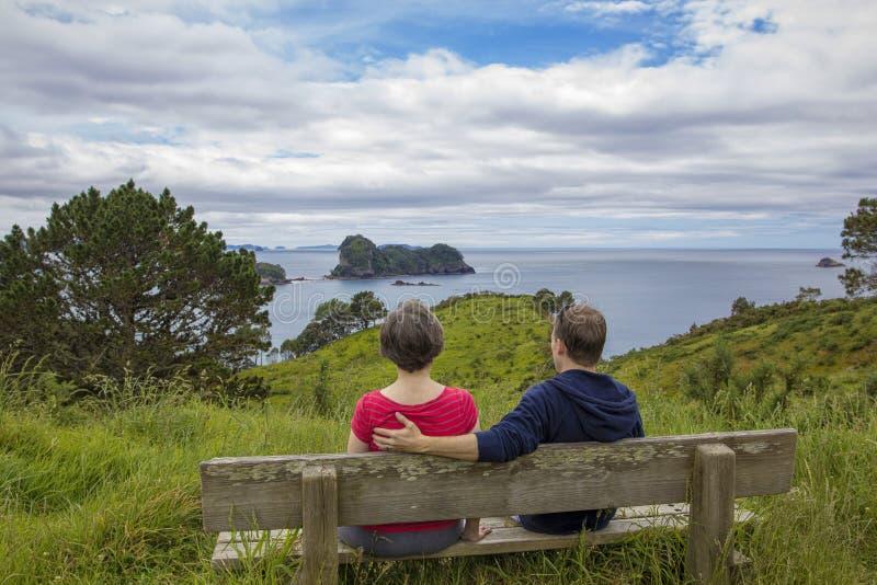享受一个美好的海景的男人和妇女在新西兰 库存图片