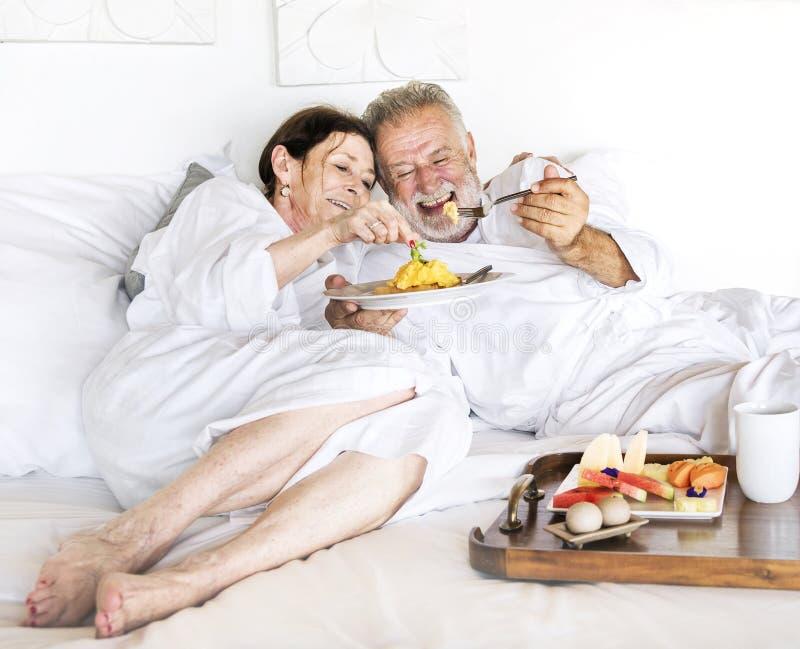 享受一些客房服务的一对资深夫妇 免版税图库摄影