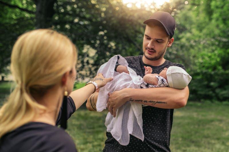 享受一天的慈爱的父母外面与他们的男婴 免版税库存图片
