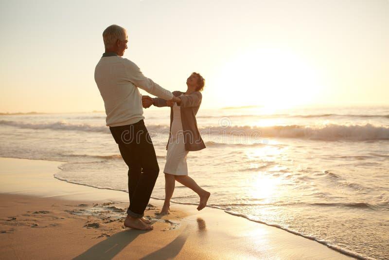 享受一天的浪漫资深夫妇在海滩 免版税库存照片