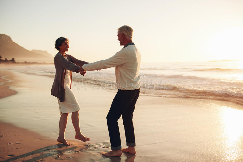 享受一天的浪漫资深夫妇在海滩 库存照片