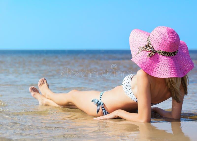 享受一天的美丽的少妇在海滩 免版税库存照片