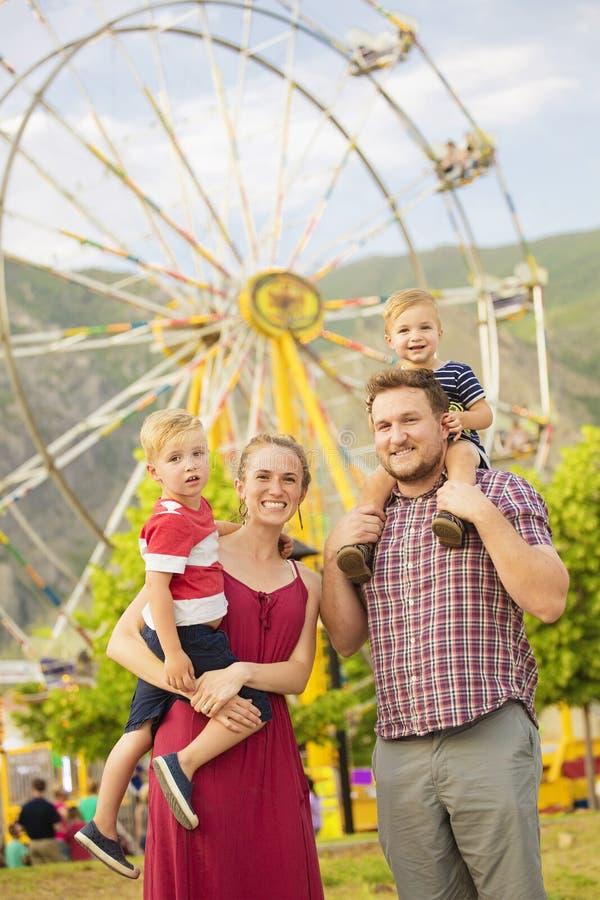 享受一天的逗人喜爱的年轻家庭在游乐园 免版税库存图片