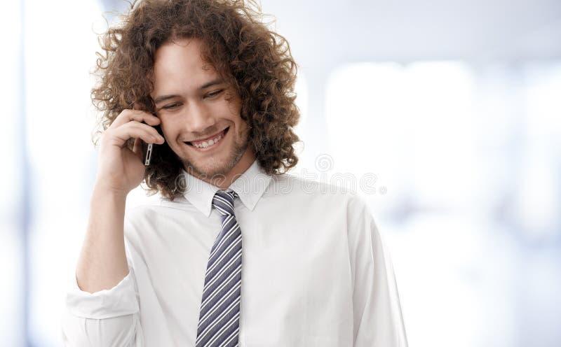 享受一次电话交谈的年轻英俊的人 免版税库存照片