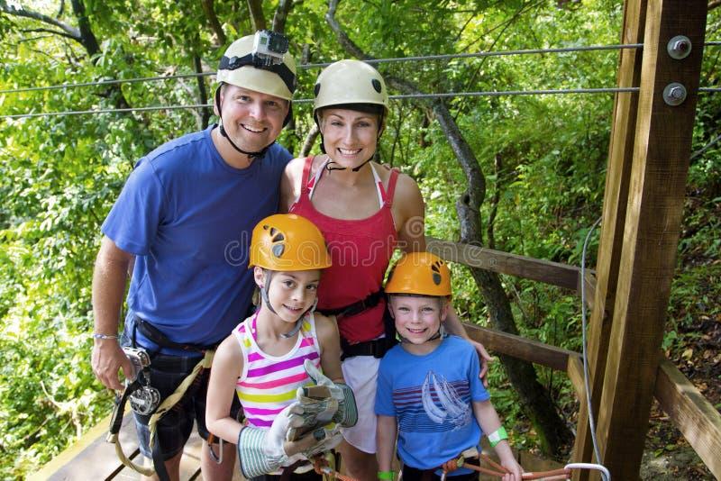 享受一次Zipline冒险的家庭在度假 免版税库存照片