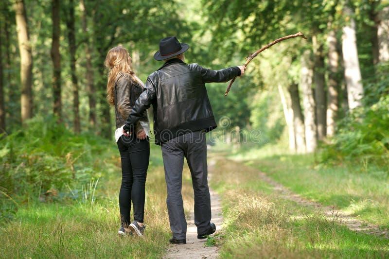 享受一走的父亲和女儿在森林里 免版税库存照片