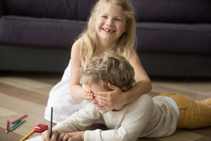 享受一起使用的愉快的逗人喜爱的兄弟姐妹,姐妹闭合值的增殖比 库存照片
