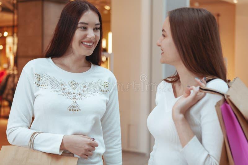 享受一起购物的年轻女人在购物中心 图库摄影
