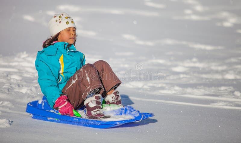 享受下坡雪撬乘驾III的女孩 库存图片