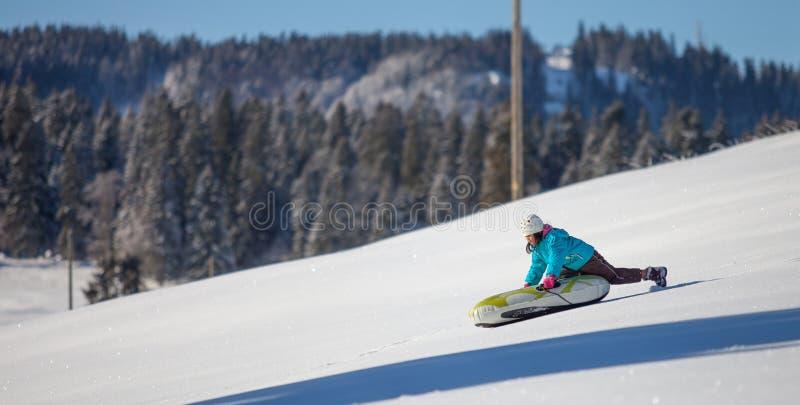 享受下坡雪撬乘驾IV的女孩 库存图片