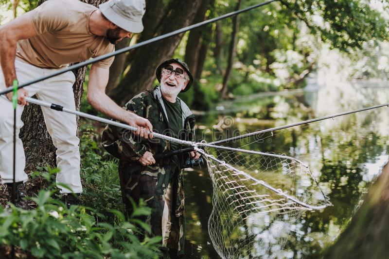 享受与他的儿子的快乐的年长渔夫周末 图库摄影