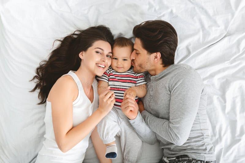享受与可爱的婴孩的正面年轻父母愉快的早晨 库存图片