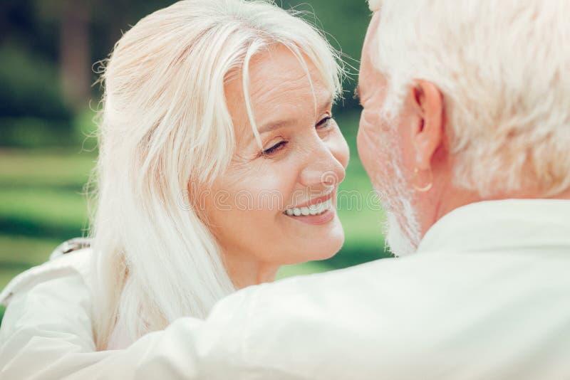 享受与她的丈夫的愉快的正面妇女时间 免版税库存图片