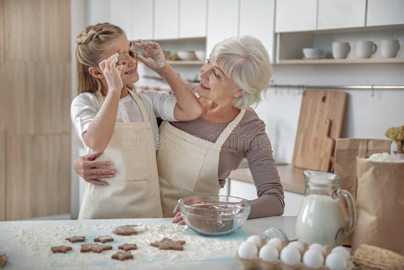 享受与她的祖母的无忧无虑的孩子烘烤法 图库摄影
