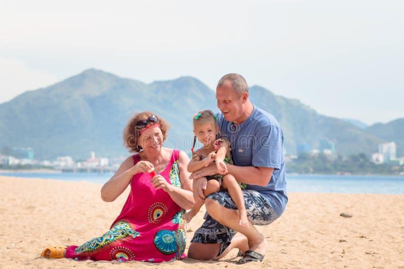 享受与孙女的祖父母天,当吹在海滩的肥皂泡在海附近时 库存图片